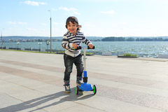 Little boy with three-wheeled scooter Royalty Free Stock Photography