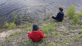 Little boy throwing rocks on the muddy bank of a river stock video
