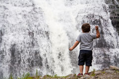 Boy near a waterfall Stock Photo