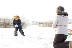 Little boy throwing snowballs at his mother Stock Photography