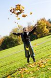 Little boy throwing up  autumn  leafes Stock Photography