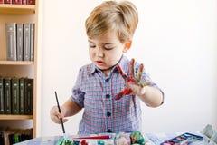 Little Boy thuis gebruikend Waterkleuren aan Verf royalty-vrije stock foto's