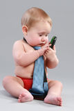 Little boy in tie play with cell phone. On a grey background Royalty Free Stock Images