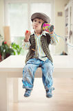 Little boy with a tin can telephone. Cute little boy in vintage outfit sitting on a table and eating strawberry while playing with a tin can telephone Stock Photography