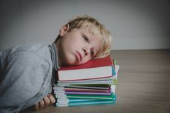 Little boy tired stressed of doing homework, bored, exhausted. Little boy bored tired exhausted stressed of doing homework and learning stock photography