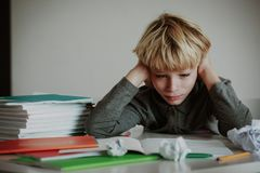 Little boy tired stressed of doing homework, bored, exhausted. Overload stock photos