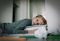 Little boy tired stressed of reading, doing homework. Little boy tired stressed exhausted of reading, doing homework stock images