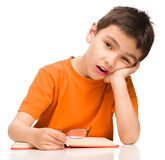 Little boy is tired to read his book. Isolated over white Royalty Free Stock Images