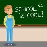 Little boy to write with chalk on the school blackboard. Royalty Free Stock Photo