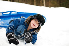 Little boy tobogganing. Little boy outdoors in winter with a toboggan Royalty Free Stock Photography