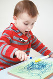 Little boy toddler drawing in album with markers Stock Photo