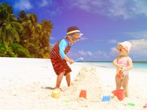 Little boy and toddler girl building sandcastle on Stock Photography