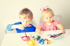Little boy and toddler girl painting eggs for Royalty Free Stock Images
