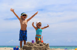 Little boy and toddler girl play with sand on beach royalty free stock photos