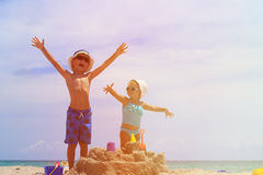 Little boy and toddler girl play with sand on beach Royalty Free Stock Photography