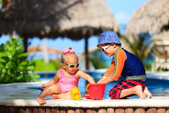 Little boy and toddler girl playing at beach Stock Photo