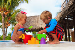 Little boy and toddler girl playing in swimming Stock Photos