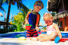 Little boy and toddler girl playing in swimming Royalty Free Stock Images