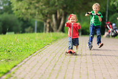 Little boy and toddler girl riding scooters in Royalty Free Stock Photo
