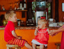 Little boy and toddler girl sitting at the bar, kids eating out Royalty Free Stock Photo