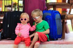 Little boy and toddler girl sitting on suitcases ready to travel Royalty Free Stock Photo