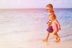 Little boy and toddler girl walk on summer beach Royalty Free Stock Photography