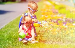 Little boy and toddler girl watering flowers in Royalty Free Stock Photo