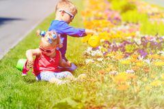 Little boy and toddler girl watering flowers in Stock Photos