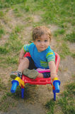 Little boy toddler playing with colorful children& x27;s plastic building wheelbarrow Stock Photo