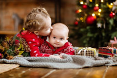 Little boy toddler in a red sweater kisses his older sister, lyi stock image