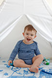 Little boy toddler in a striped tank top sitting in the teepee stock photo