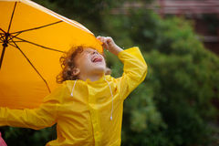 The little boy tongue catches rain drops. Royalty Free Stock Images