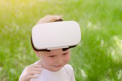 Little boy took off his virtual reality helmet. Green grass on t. He background stock photo