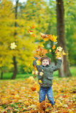 Little boy tossing leaves in autumn park Royalty Free Stock Photos