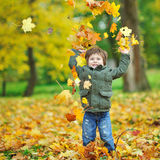 Little boy tossing leaves in autumn park Stock Photos