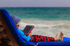 Little boy with touch pad at the beach Royalty Free Stock Photos