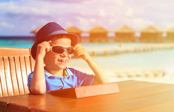 Little boy with touch pad at tropical resort Royalty Free Stock Images