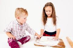 Little boy touching raw dough near sister royalty free stock photo