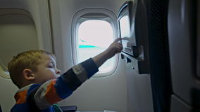 Little boy touching seat monitor in plane stock video footage