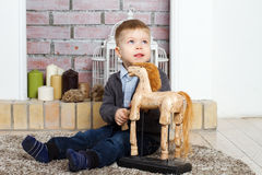 Little boy and toy. Little boy sits on a floor with toy horse Stock Images