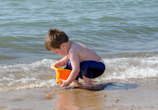 Little boy with toy bucket on the beach Stock Photos