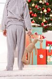 Little boy and toy bunny at christmas. Little boy in pyjama and toy bunny handheld standing at christmas tree waiting for presents in morning Stock Photo