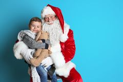Little boy with toy bunny sitting on authentic Santa Claus` lap. Ttle boy with toy bunny sitting on authentic Santa Claus` lap against color background stock photo