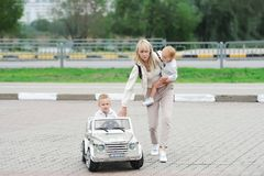 Little boy in toy car. Happy mother and her little children in the park royalty free stock photo