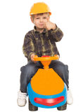 Little boy on a toy car and a helmet Stock Image