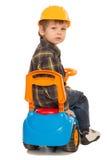 Little boy on a toy car and a helmet Royalty Free Stock Photos