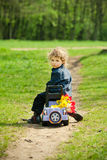 Little boy on a toy-car in park Royalty Free Stock Image