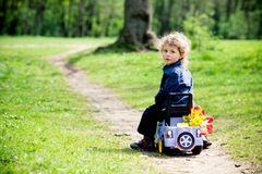 Little boy on a toy-car in park Royalty Free Stock Photography