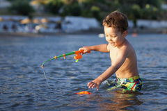 Little boy and toy fishing pole. Little boy playing with toy fishing pole and magnetic fish in the sea at sunset stock photography