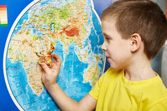 Little boy with toy giraffe shows Africa on world map Royalty Free Stock Images
